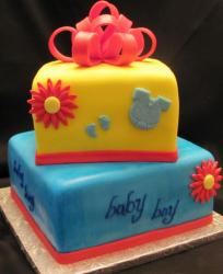 Two tier yellow and blue baby shower cake for baby boy with red bow.JPG
