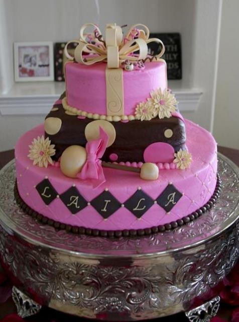 Three tier pink and brown baby shower cake with white bow.