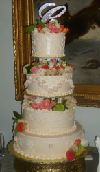 Big classic wedding cake with full of fresh flowers on big monogram topper.PNG