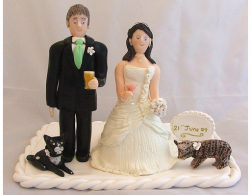 Bride and groom cake toppers with their cats.PNG