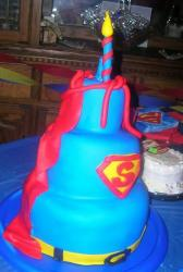 Blue 3 tier Superman theme cake with red cape.JPG