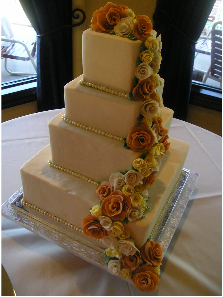 Cream elegant floral wedding cake in four tiers.PNG