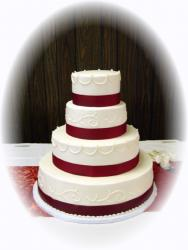 classic white wedding cake with dark red ribbons pic
