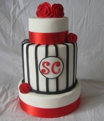 Three tier white round cake with striped middle section and red roses.JPG