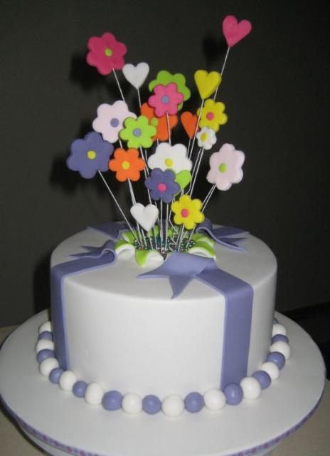 Round White Cake With Fondant Flowers Popping Out Of The