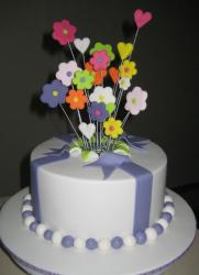 Round white cake with fondant flowers popping out of the middle.JPG