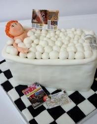 Red hair woman relaxing in bubble bath with magazines cake.JPG
