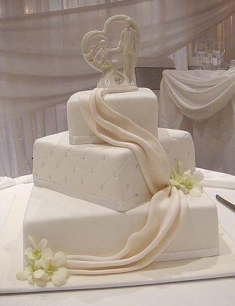 Three Tier Elegant White Wedding Cake With Drape And White
