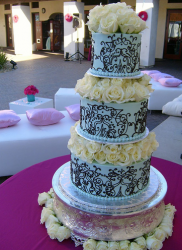 Chic blue wedding cake with chocolate patterns with white roses cake topper.PNG