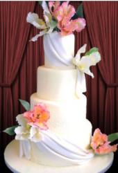 Four-tier white round column wedding cake with white draps and carnations.JPG