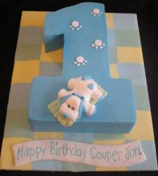 Cute first birthday cake in shape of the numer one with pink puppy on top.JPG