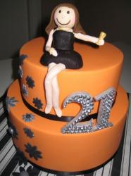 Two tier orange cake with woman in black dress for 21st birthday.JPG