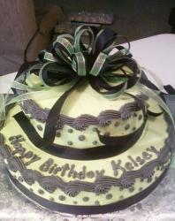 Two tier birthday cake with black bow and velvet cream.JPG