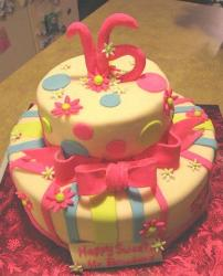 Two tier light yellow sweet 16 birthday cake with pink bow.JPG