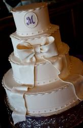 Four tier circular wedding cake with monogram and white bow.JPG