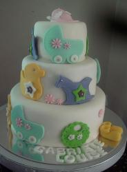 Three tier white baby shower cake with baby carriers and toys and shoes.JPG