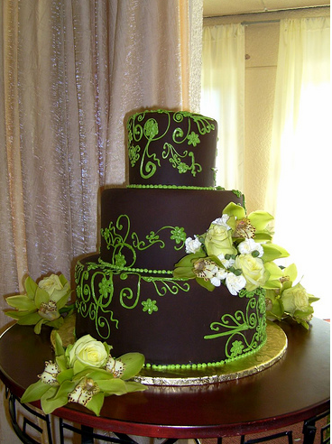 Beautiful wedding cake in dark chocolate with green patterns and tropical fresh flowers.PNG