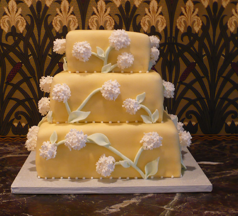 Three tier  yellow cake with white floral decor picture.PNG
