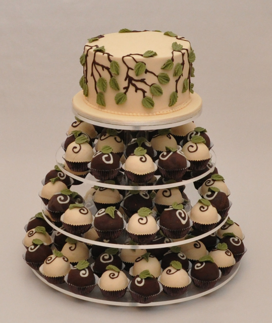 Cake and cupcakes with white and dark chocolate with green leaves cake ...