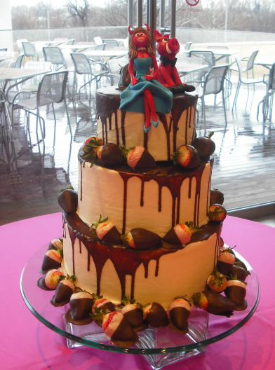 Three tier chocolate wedding cake with chocolate covered strawberries and red horned bride and groom toppers.JPG