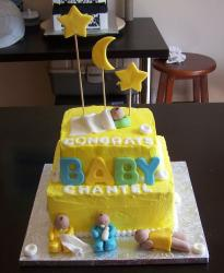 Two tier yellow baby shower cake with four babies.JPG