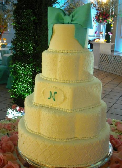 Five tier ivory wedding cake with green cloth wedding bow topper.JPG