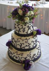 Three tier round wedding cake with purple flowers and white roses.JPG