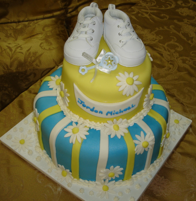 Yellow and blue baby shower cake with daisies, booties and rattle.PNG