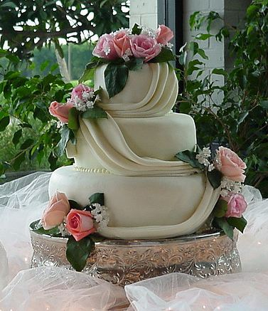 Three tier white round wedding cake with drapes and pink roses.JPG