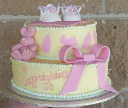 Yellow baby shower cake with baby shoes topper and rabbit with big pink bowl.PNG