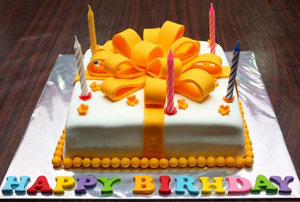 White birthday cake with large orange ribbon and Happy Birthday letters in various colors.JPG