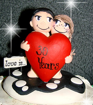 comical wedding cake toppers with couple holding a big heart.PNG