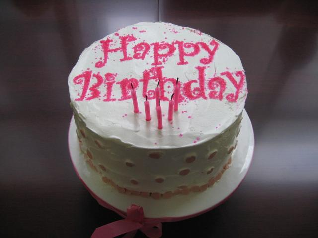 white birthday cake with pink letters and pink candles.jpg