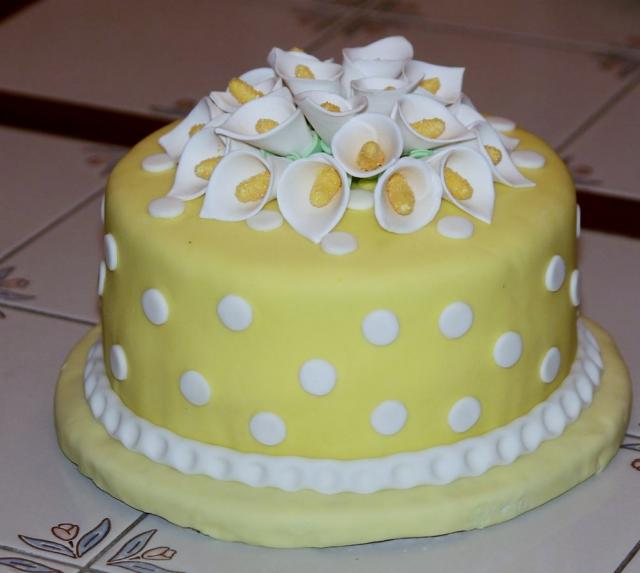 Round yellow cake with white flowers on top & white ...