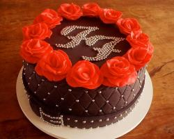 Round elegant chocolate cake with monogram and red roses on top.JPG