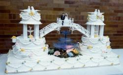 Unique Double Wedding Cake connected by bridge with bride & groom & fountain in the middle.JPG
