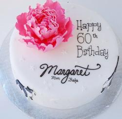 Round white 60th birthday cake with pink flower and cursive writing.JPG