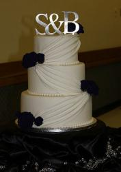 Three tier ivory wedding cake with silver monogram topper and black roses.JPG