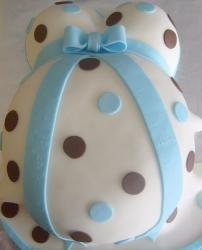 White pregnant body baby shower cake with light blue ribbon and pokadots