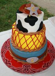 Three tier cowboy theme cake with hat and belt buckle.JPG