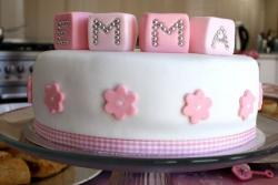 White round baby shower cake with pink play blocks on top.JPG
