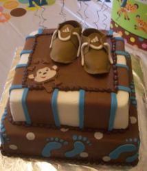 Two tier square baby shower cake in brown with footprints and monkey and baby shoes.JPG