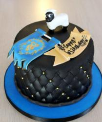 Round black leather theme cake with white sheep on top.JPG