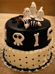 Two tier black and white Halloween cake with ghosts on top.JPG