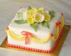 Square white cake with yellow drapes and white and yellow flowers on top.JPG