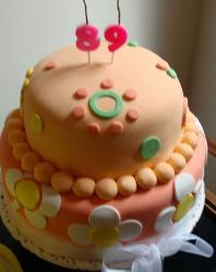 Two tier peach color birthday cake with pearls and white flower patterns.JPG