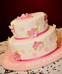 Two tier white first birthday cake with pink pokadots and flowers.JPG