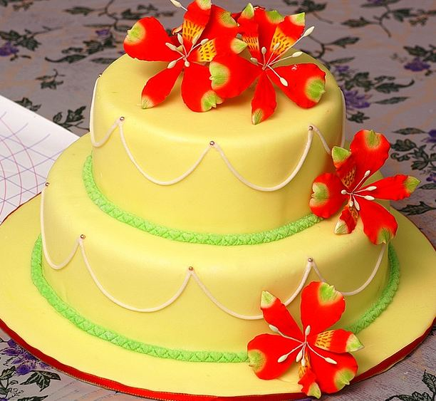 Two tier yellow wedding cake with red flowers.JPG