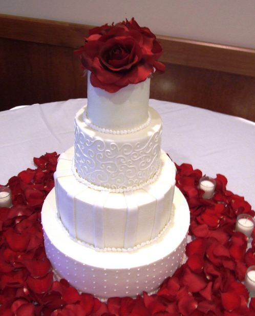 Four Tier White Wedding Cake With Red Rose On Top With Rose Petals AroundJPG 1 Comment
