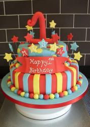 Two tier first birthday cake with red number one on top and banner.JPG